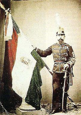 Földváry Károly honvéd ezredes az olaszországi magyar légió zászlajával. Színezett fénykép (1863)