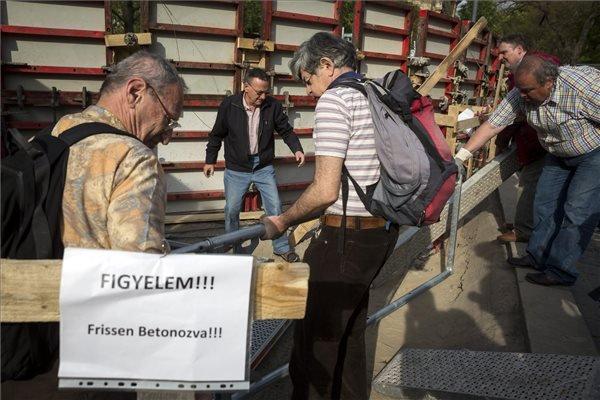 Tiltakozók lebontják a német megszállás áldozatainak tiszteletére tervezett emlékmű helyét elkerítő kordont Budapesten a Szabadság téren 2014. április 18-án. Tiltakozók a kordont többször is elbontották már, de az építők mindig visszaállították. MTI Fotó: Mohai Balázs