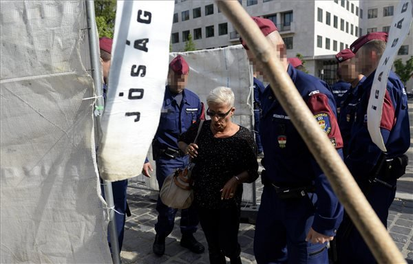 Zoltai Andreát, a demonstráció egyik szervezőjét (b2) rendőrök vezetik ki a Szabadság térre tervezett német megszállás áldozatainak emlékműve építési területéről 2014. április 29-én. A rendőrök egyenként távolították el az emlékmű építési területéről azokat a demonstrálókat, akik a német megszállás áldozatainak emlékműve megépítése ellen tiltakoztak. MTI Fotó: Bruzák Noémi